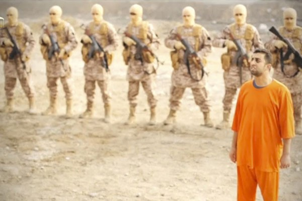 Seorang pria yang diduga bernama Moaz Al-Kassasbeh, pilot Jordania, berdiri di depan sekelompok orang bersenjata (foto: Reuters)
