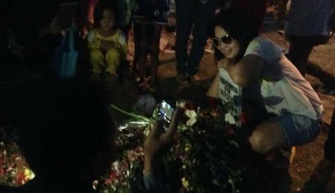 Seorang wanita berfoto selfie di depan makam Olga Syahputra (foto: vivanews)