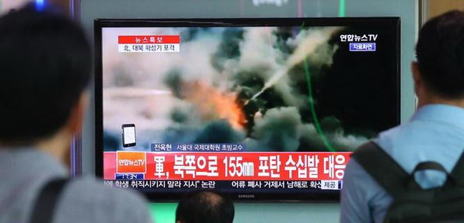 Komuter di stasiun kereta api Seoul melihat berita tentang serangan roket di perbatasan Korea Utara-Selatan (foto: Yonhap/Agence France-Presse — Getty Images )