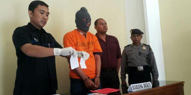Paur Subag Humas Polres Madiun Kota, Aiptu Mashudi, menunjukkan barang bukti judi togel online (foto: Kompas)