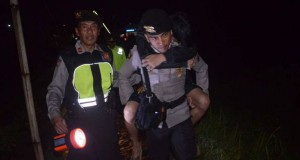 Petugas polisi resort Wonosobo mengggendeng salah seorang pendaki yang mengalami luka-luka akibat tersambar petir saat melakukan pendakian di kawasan Gunung Prau, Minggu (23/4/2107) malam. (Dok. Bid Humas Polda Jateng)