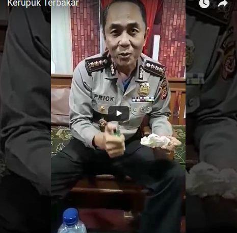 Seorang polisi membuktikan kandungan plastik di sebuah kerupuk