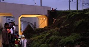 Sejumlah petugas gabungan dari badan SAR dan Pemadam Kebakaran Bandara Soetta melakukan evakuasi terhadap korban longsor tembok under pass perlintasan Kereta Bandara Soetta di kawasan Parimeter Selatan, Bandara Soekarno Hatta, Tangerang, Banten, Senin (5/2) malam. Hingga Foto ini disiarkan petugas gabungan masih melakukan evakuasi satu orang pengendara motor dan dua orang yang berada dalam satu mobil, ambruknya dinding under pass tersebut diduga karena kurang kuatnya konstruksi serta curah hujan yang tinggi yang mengguyur kawasan tersebut. ANTARA FOTO/Muhammad Iqbal/foc/18.